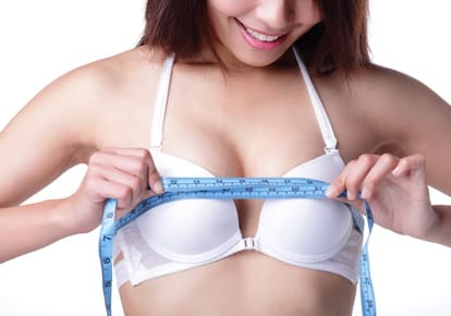 young woman checking her breast measurement isolated over white background, asian